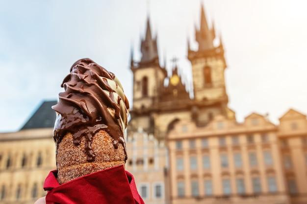 Ręka trzyma tradycyjne czeskie trdelnik cookie na scenie starego miasta w pradze