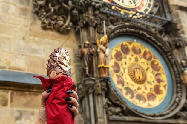 Ręka trzyma tradycyjne czeskie trdelnik cookie na scenie zegara astronomicznego w pradze