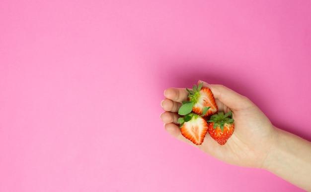 Ręka trzyma truskawkę na różowym tle. baner płaski świeckich. miejsce na tekst. abstrakcyjny.