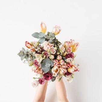 Ręka trzyma tulipan, bukiet kwiatów eukaliptusa na białej ścianie