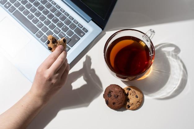 Ręka trzyma ugryziony plik cookie z kawałkami czekolady obok laptopa, filiżankę herbaty, dwa ciasteczka w słońcu, widok z góry.