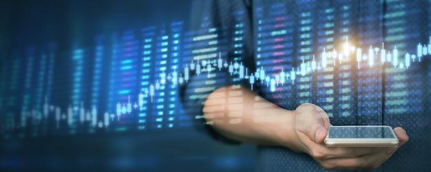Ręka trzyma urządzenie smartphone i dotykając ekranu. przedsiębiorca biznesmen patrząc na świecę analizy wykresów