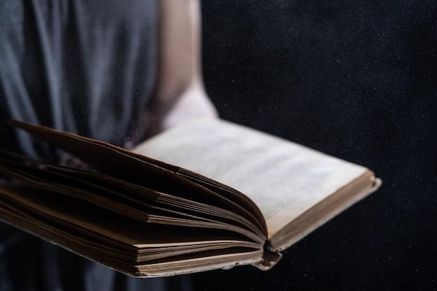 Ręka trzyma vintage otwartą książkę świeci na czarnym tle
