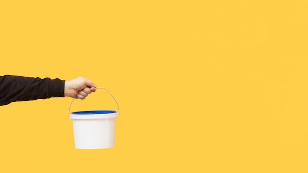 Ręka trzyma wiadro do malowania ścian