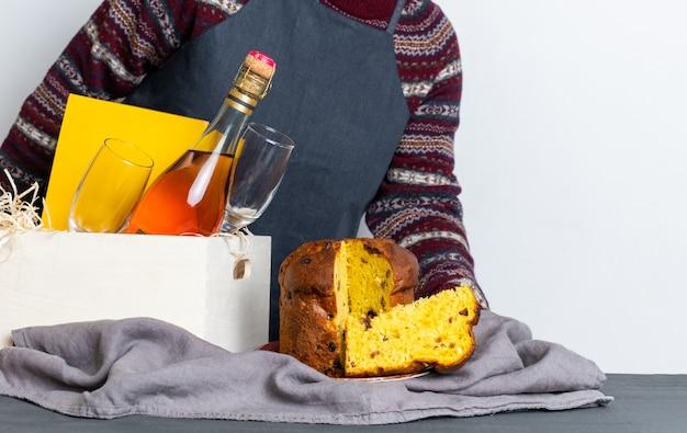 Ręka trzyma wielkanocny panetone włoski kawałek w pobliżu pudełka z butelką szampana.