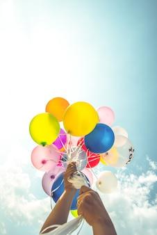 Ręka trzyma wielobarwne balony wykonane z efektem filtra retro vintage.