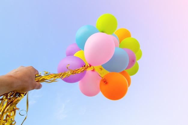 Ręka trzyma wielokolorowe balony