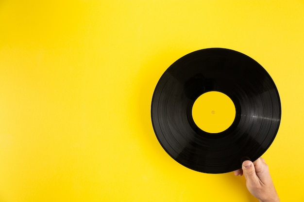 Ręka trzyma winylowego rejestr na abstrakcjonistycznym żółtym tle