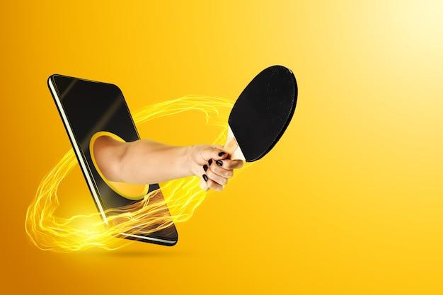Ręka trzyma wiosło do ping ponga przez smartfona