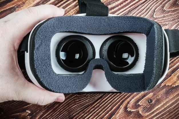 Ręka trzyma wirtualnych szkła na drewnianym tle