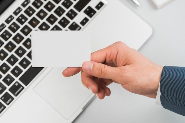 Ręka trzyma wizytówkę w biurze