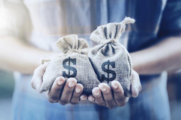 Ręka trzyma worek pieniędzy. koncepcja oszczędzania finansów i księgowości