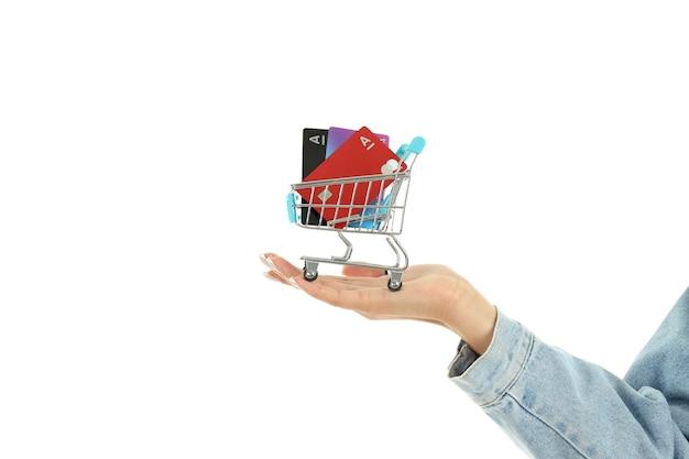 Ręka trzyma wózek sklepowy z kartami kredytowymi, na białym tle.