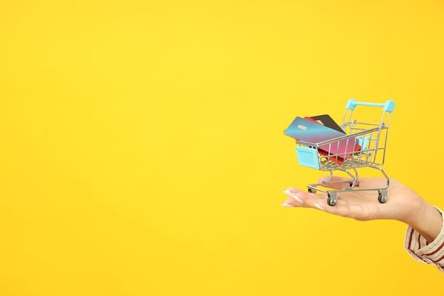 Ręka trzyma wózek sklepowy z kartami kredytowymi na żółtym tle.