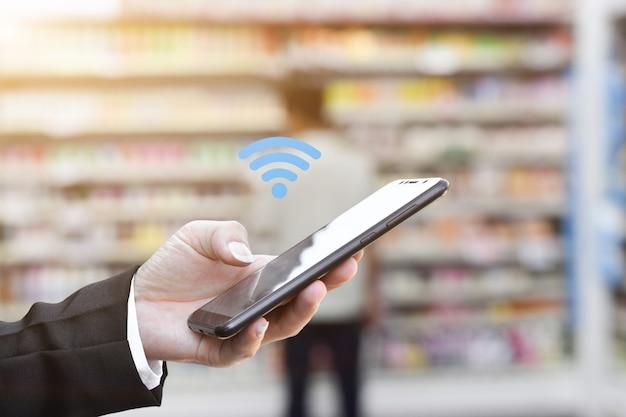 Ręka trzyma za pomocą mobilnego smartfona z ikoną wifi. pomysł na komunikację biznesową w sieci społecznościowej.