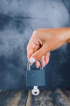 Ręka trzyma zamkniętą kłódkę