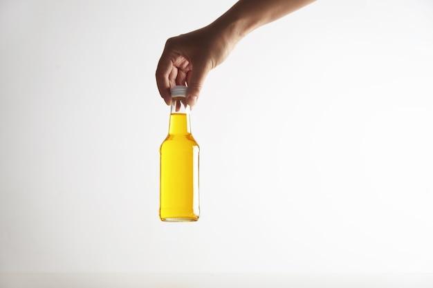Ręka trzyma zamkniętą rustykalną szklaną butelkę z pysznym zimnym napojem w środku