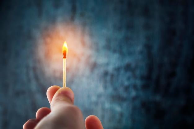 Ręka trzyma zapałkę, oświetla ciemność płomieniem.