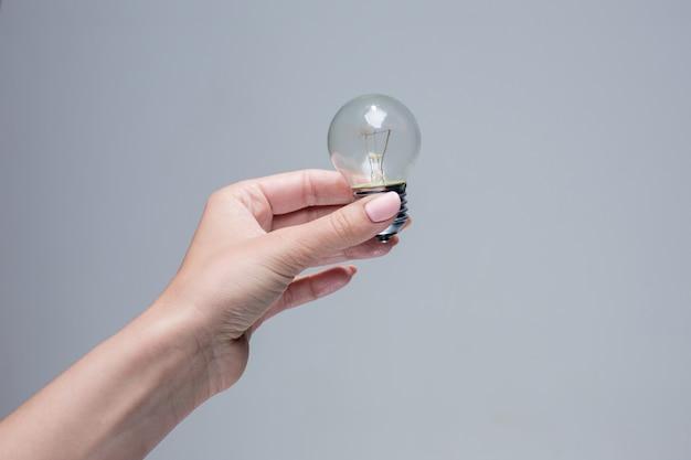 Ręka trzyma żarową żarówkę na szarości przestrzeni