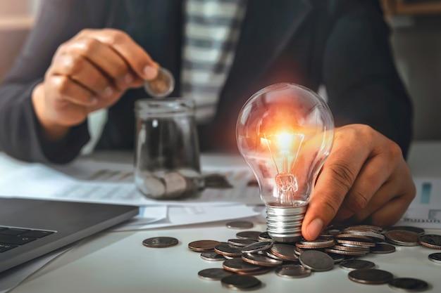Ręka trzyma żarówkę i wkłada monety do dzbanka. pomysł z innowacją i inspiracją