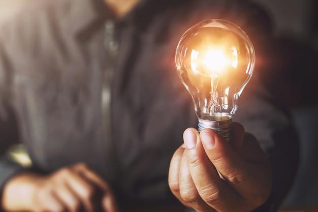 Ręka trzyma żarówkę. koncepcja pomysłu z innowacją i inspiracją