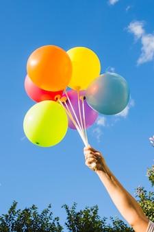 Ręka trzyma zbiór jasnych balonów