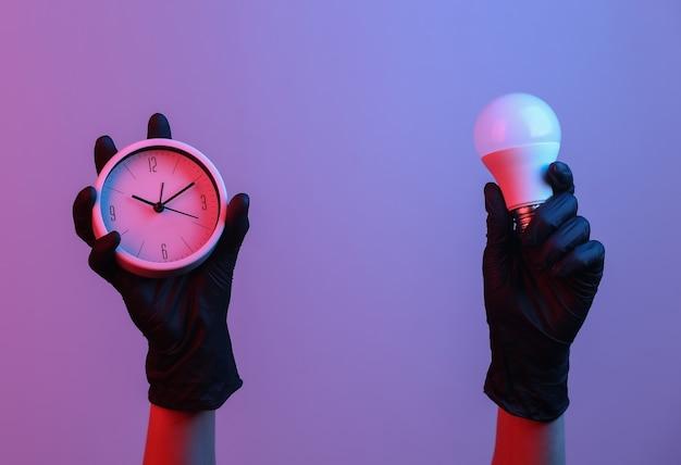Ręka trzyma zegar i żarówkę w różowym niebieskim neonowym świetle gradientowym