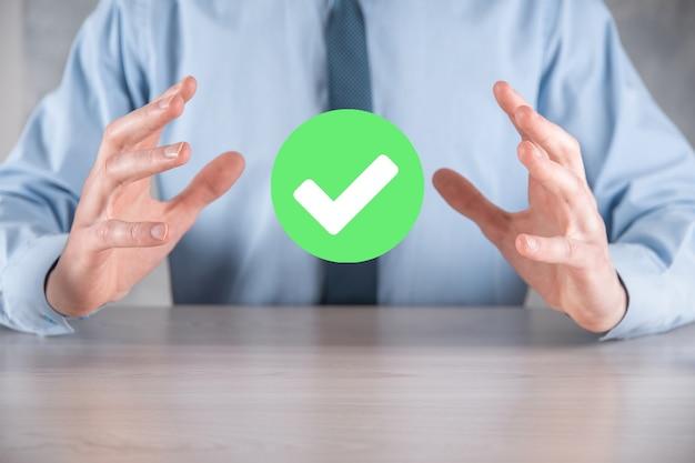 Ręka trzyma zieloną ikonę znacznik wyboru, znak znacznika wyboru, zaznacz ikonę, prawy znak, okrąg zielony przycisk znacznika wyboru, gotowe.na ciemnym tle.banner.skopiuj miejsce.miejsce dla tekstu.