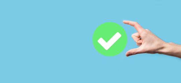 Ręka trzyma zieloną ikonę znacznik wyboru, znak znacznika wyboru, zaznacz ikonę, prawy znak, okrąg zielony przycisk znacznika wyboru, sporządzono.na ciemnym tle.banner.skopiuj miejsce.miejsce dla tekstu.