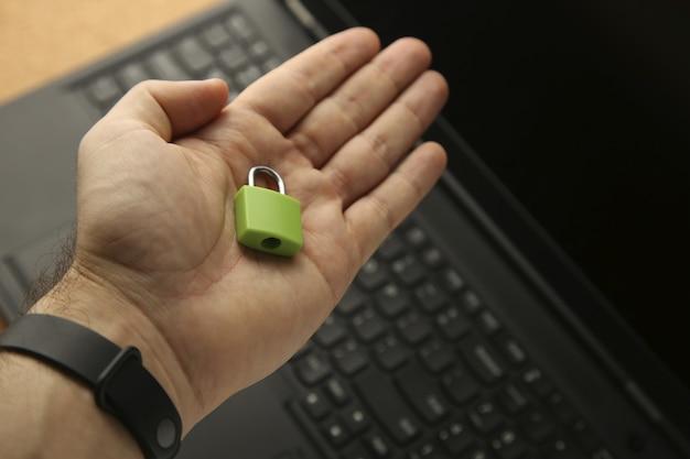 Ręka trzyma zieloną kłódkę z laptopem w tle. koncepcja bezpieczeństwa cybernetycznego.