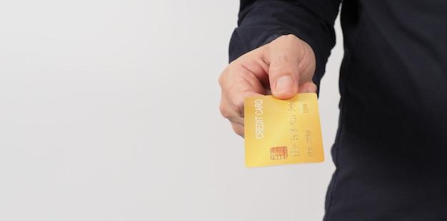Ręka trzyma złotą kartę kredytową na białym tle. azjatycki mężczyzna ręka.