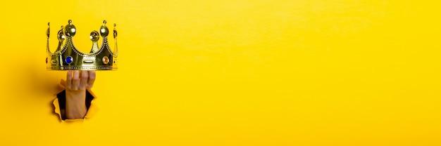 Ręka trzyma złotą koronę na jasnożółtym tle