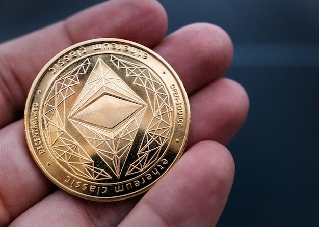 Ręka trzyma złotą monetę eth. ethereum to zdecentralizowany blockchain typu open source z inteligentną umową. koncepcja kryptowalut i zdecentralizowanych finansów