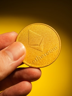 Ręka trzyma złotą monetę z symbolem ethereum. koncepcja waluty cyfrowej.