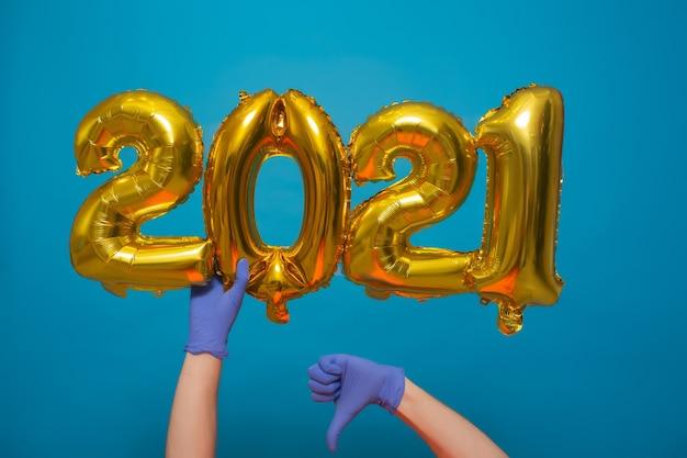 Ręka trzyma złote balony z helem. pokaż kciuk w dół.
