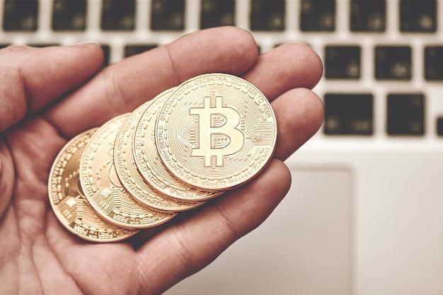 Ręka trzyma złote bitcoiny
