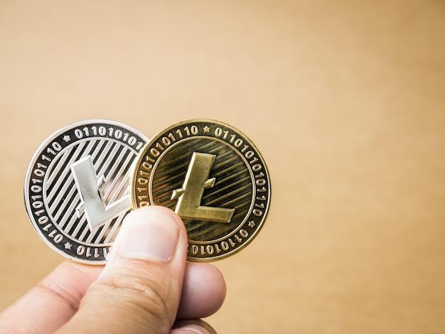 Ręka trzyma złote i srebrne monety litecoin.
