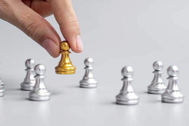 Ręka trzyma złote pionki szachowe