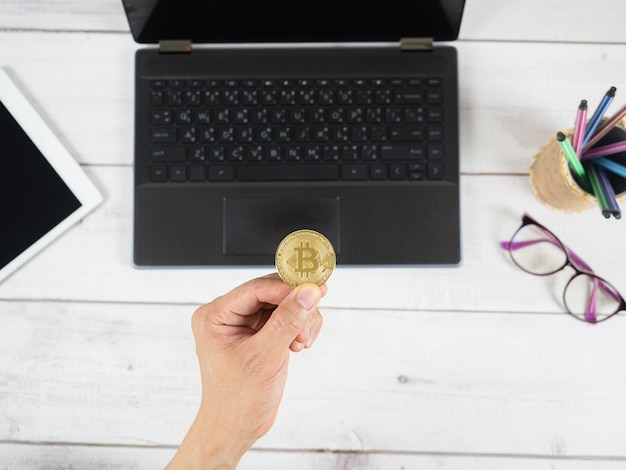 Ręka trzyma złoty bitcoin i telefon komórkowy z laptopem i tabletem na tle stołu z drewna