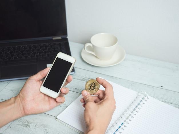 Ręka trzyma złoty bitcoin i telefon komórkowy z obszarem roboczym na białym tle stołu z drewna