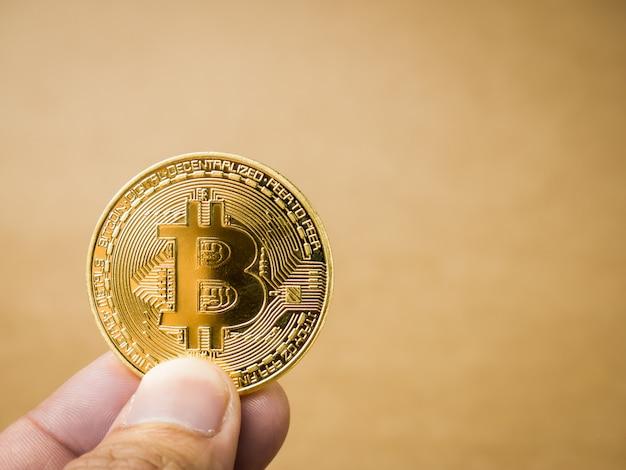 Ręka trzyma złoty bitcoin.