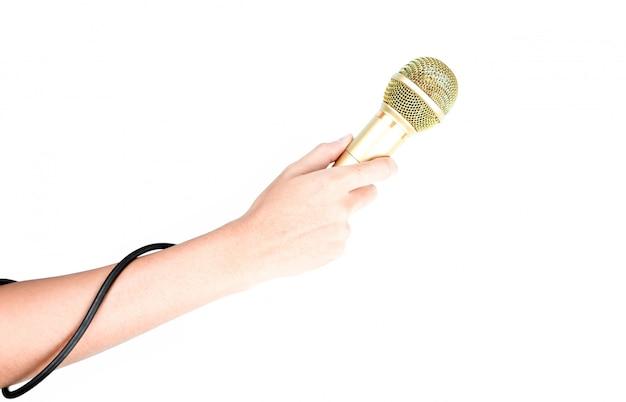 Ręka trzyma złoty mikrofon na białym tle