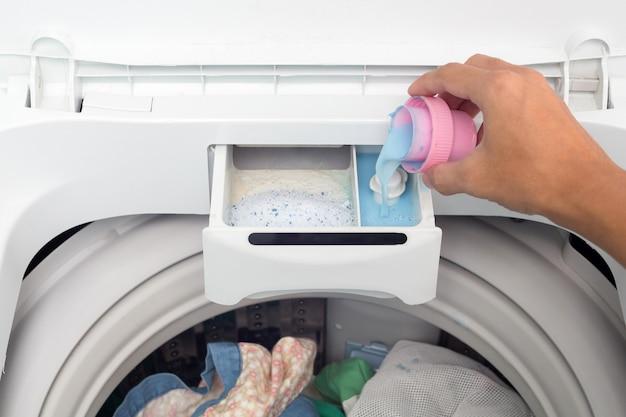 Ręka trzyma zmiękczacz do tkanin w pralce.