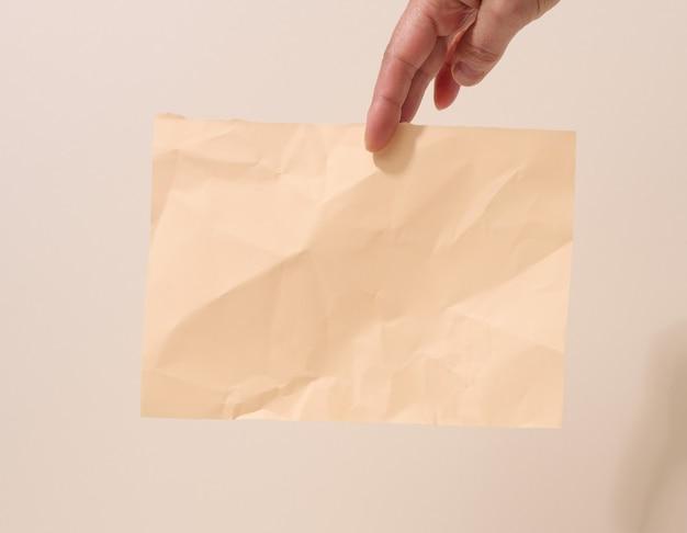 Ręka trzyma zmiętą kartkę papieru na beżowym tle. miejsce na napisy i ogłoszenia