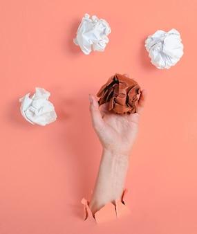 Ręka trzyma zmięte kulki papieru przez podarty żółty papier. koncepcja biznesowa minimalistyczny pomysł