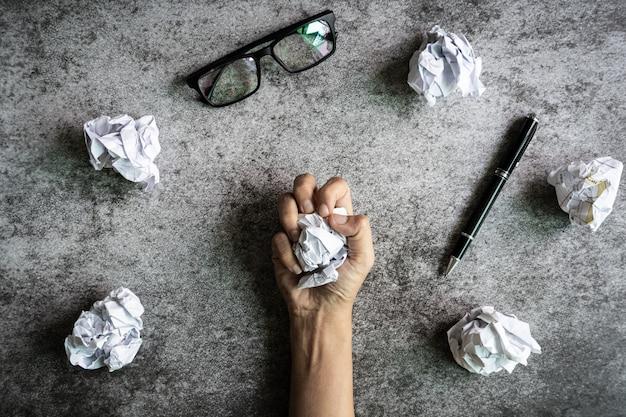 Ręka trzyma zmięte papierowe piłki na grunge
