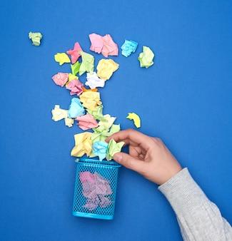 Ręka trzyma zmięte wielobarwne kawałki papieru