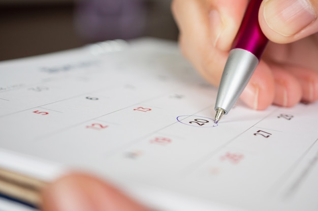 Ręka trzyma znak koło pióra na datę w kalendarzu