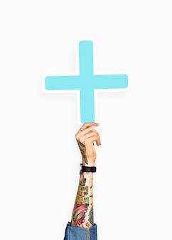 Ręka trzyma znak plus