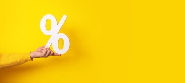 Ręka trzyma znak procentu na żółto